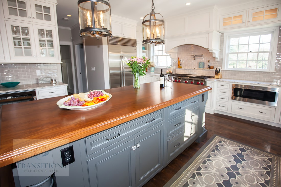 Gray island cabinetry with wood countertop