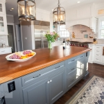 Traditional kitchen design with gray island and wood countertop